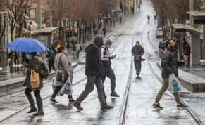 Israelis are seen walking along the Jaffa Street light rail tracks in the rain amid the coronavirus lockdown, on January 19, 2021.