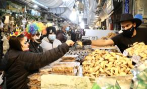Israelis in Purim costume buy hamentashen from a Mahaneh Yehuda seller.