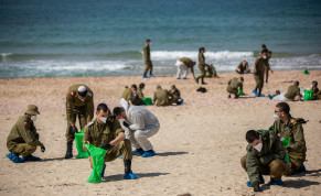 SOLDIERS CLEAN tar off Palmahim beach on Monday, following an offshore oil spill that drenched most of the Israeli coastline.