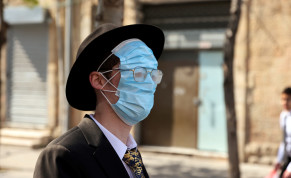 An ultra-Orthodox man wears three masks over his face while celebrating Purim amid coronavirus disease (COVID-19) restrictions in Jerusalem February 28, 2021