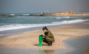 Israeli soldiers clean tar off the Palmachim beach following an offshore oil spill which drenched most of the Israeli coastline, February 22, 2021