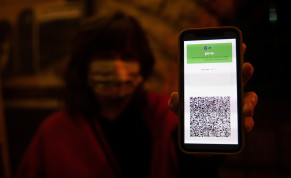 A woman shows her green passport at the Khan theater in Jerusalem on February 23, 2021.