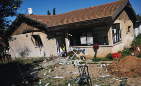 A MUNICIPAL worker sits at the entrance to a damaged house after a rocket fired from Gaza landed in Sderot, February 2009.