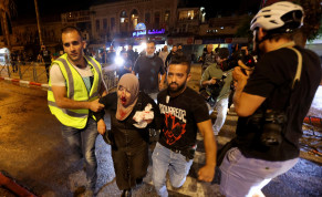 An injured Palestinian woman is evacuated during clashes with Israeli police near Damascus Gate on Laylat al-Qadr during the holy month of Ramadan, in Jerusalem's Old City, May 8, 2021.