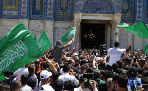 People hold Hamas flags as Palestinians gather after performing the last Friday of Ramadan to protest over the possible eviction of several Palestinian families from homes on land claimed by Jewish settlers in the East Jerusalem neighborhood of Sheikh Jarrah, May 7, 2021.