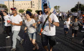 Israelis take cover as a siren sounds warning of incoming rockets from the Gaza Strip, during Jerusalem day, in Jerusalem, May 10, 2021.