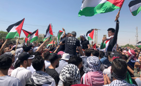 Demonstrators hold Palestinian flags during a protest to express solidarity with the Palestinian people,in Karameh, Jordan valley, May 14th, 2021.