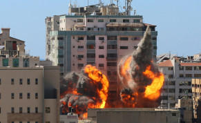 An explosion is seen near a tower housing AP, Al Jazeera offices during Israeli missile strikes in Gaza city, May 15, 2021.