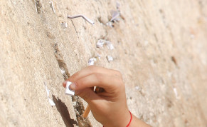 A hand putting a note into cracks in the Western Wall.