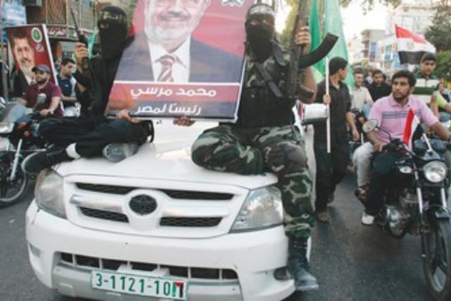 Hamas gunmen hold Morsi poster 370 (photo credit: Mohammed Salem/Reuters)