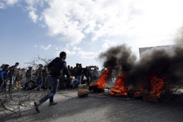 A Palestinian youth burn tires during a protest in the Jalazoun refugee camp, January 9, 2014. (photo credit: . REUTERS/Mohamad Torokman )