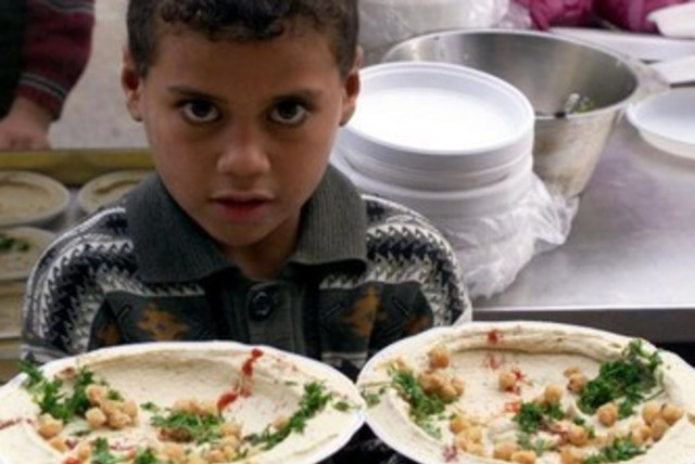 A Palestinian child in Gaza serves up dishes of hummus. (photo credit: REUTERS)