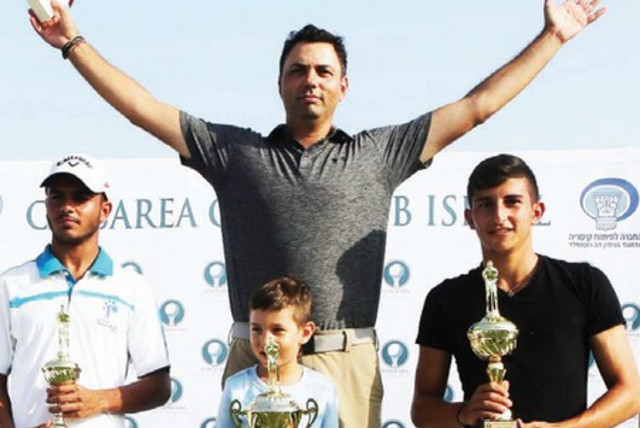 Men's Open gross-score winners at the Caesarea Club Championship – first-place Roie Edelman and his son (center), second-pace Eitan Solomon (right) and third-place Dolev Gueta (left) pose with their trophies after the tournament (photo credit: Courtesy)