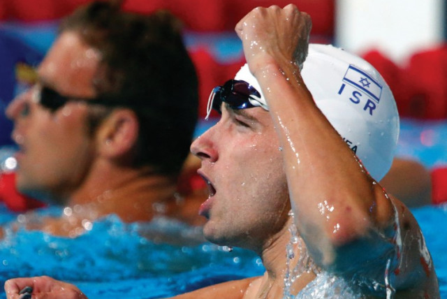 Swimmer Guy Barnea says he is especially proud to have the Israel flag on his cap in times like these. (photo credit: REUTERS)