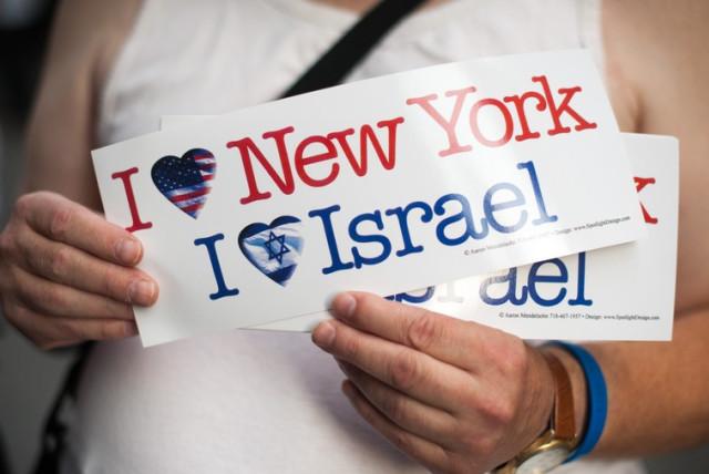 A pro-Israel demonstrator holds up stickers. (photo credit: ANNA HIATT)