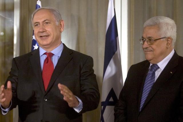 Prime Minister Benjamin Netanyahu (L) gestures as Palestinian Authority President Mahmoud Abbas looks on (photo credit: REUTERS)