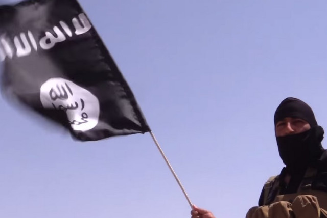 An Islamic State terrorist holds a flag with the group's insignia. (photo credit: REUTERS)