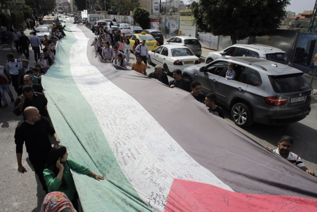 PEOPLE MARCH as they hold a large Palestinian flag in Ramallah in October (photo credit: REUTERS)