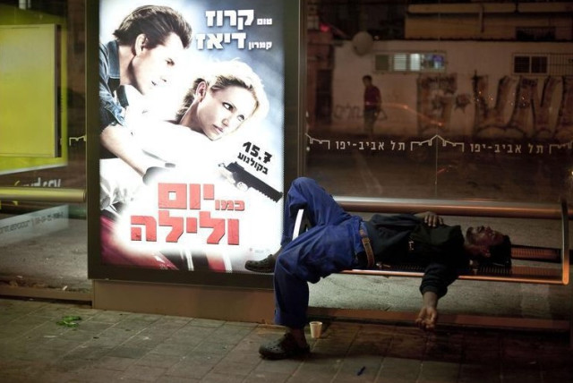 An African migrant worker sleeps on a bench of a bus station in south Tel Aviv (photo credit: REUTERS)