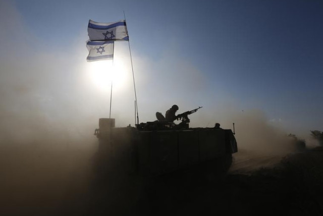 An IDF soldier rides an armored personnel carrier toward a staging area near the Gaza border (photo credit: REUTERS)