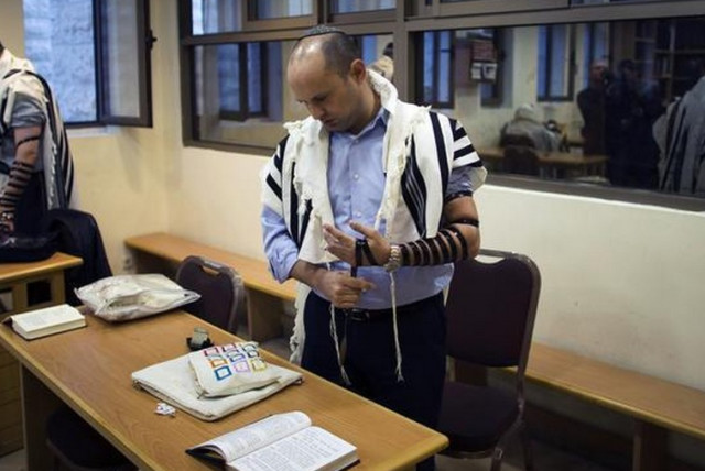 Bayit Yehudi leader Naftali Bennett prays at the Har Nof synagogue, site of a Palestinian terror attack that killed five Israelis (photo credit: REUTERS)