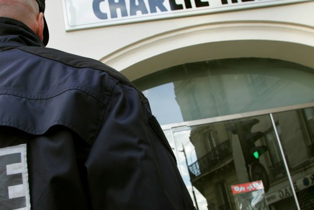 "A policeman stands guard outside the French satirical weekly ""Charlie Hebdo"" in Paris, February 9, 2006. (photo credit: REUTERS)"