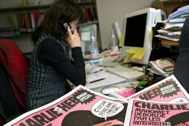 "Copies of the French satirical weekly ""Charlie Hebdo"" are seen in its Paris newsroom (photo credit: REUTERS)"