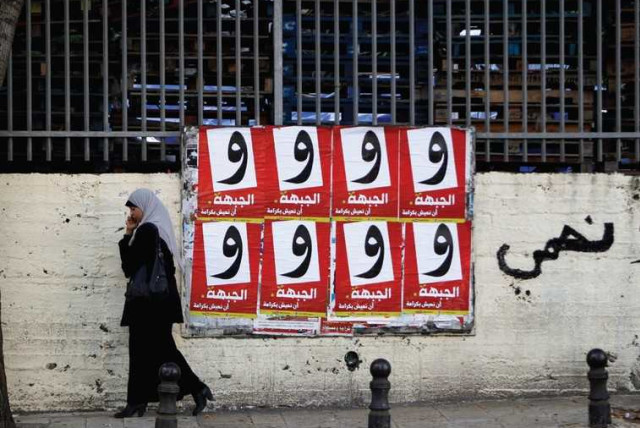 A WOMAN walks past campaign posters for the Arab-led Hadash party in the Israeli-Arab city of Umm al-Fahm (photo credit: REUTERS)