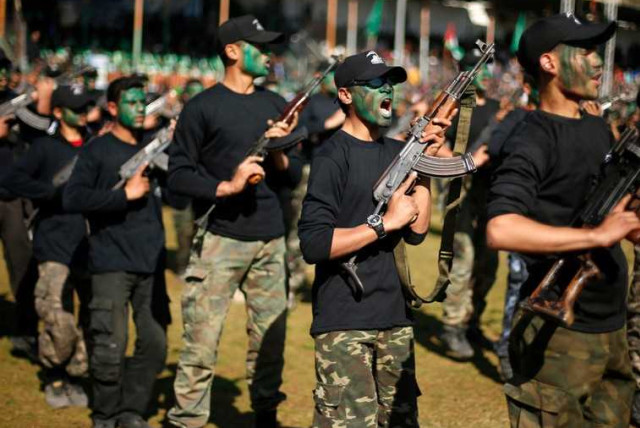 Palestinian youths hold weapons during a military-style graduation ceremony.  (photo credit: REUTERS)
