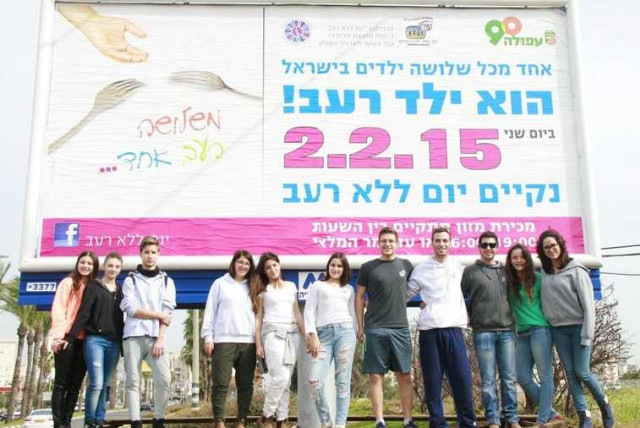 WIZO students stand under billboard in Afula for Day without Hunger (photo credit: Courtesy)