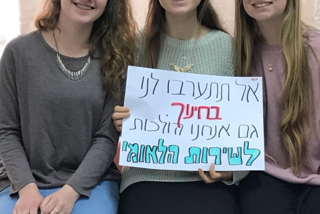 """Religious girls hold a sign that says """"Don't interefere with our education. We believe in national service"""""""