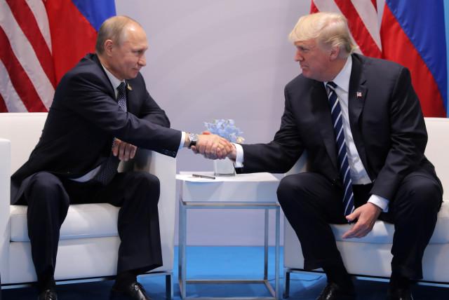 President Donald Trump shakes hands with Russia's President Vladimir Putin. (photo credit: REUTERS/CARLOS BARRIA)