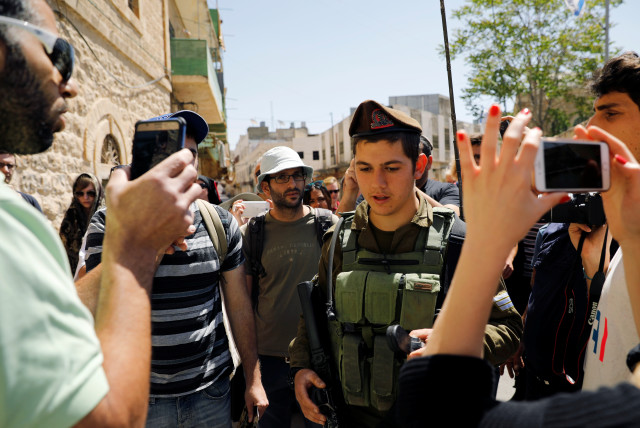 """An Israeli soldier stands between an Israeli settler (L) and visitors on a tour held by leftwing NGO """"Breaking the Silence"""" in the West Bank city of Hebron April 19, 2017. Picture taken April 19, 2017. (photo credit: REUTERS)"""