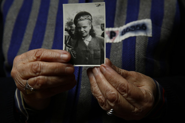 Auschwitz death camp survivor Jadwiga Bogucka holds a picture of herself from 1944 in Warsaw (photo credit: KACPER PEMPEL / REUTERS)