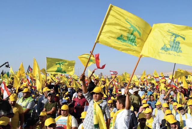 SUPPORTERS OF Hezbollah leader Sayyed Hassan Nasrallah display Hezbollah and Lebanese flags in Lebanon's Bekaa valley.  (photo credit: REUTERS)