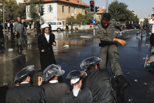 ULTRA-ORTHODOX MEN and police clash during a protest against serving in the Israeli army. (photo credit: REUTERS)