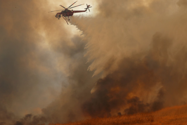 A helicopter drops water on a wind driven wildfire. (photo credit: REUTERS)