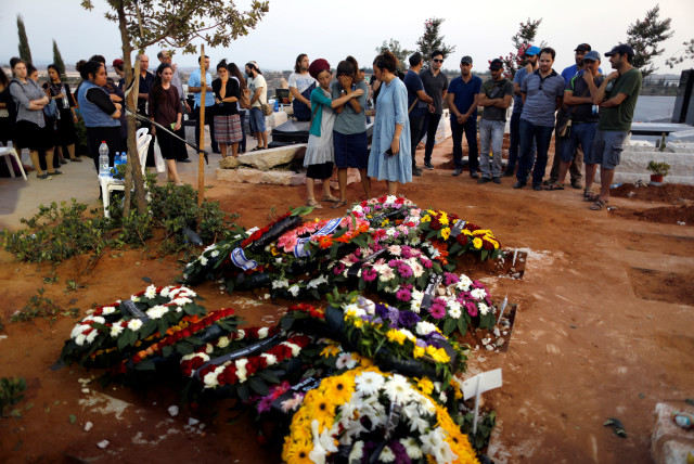 Family and friends mourn around the fresh graves of Haya, Elad and Yossi, three members of the Salomon family who were killed in a stabbing attack Friday night in the Jewish settlement of Neve Tsuf (photo credit: RONEN ZVULUN / REUTERS)