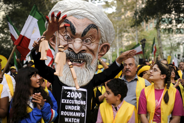 """Max Saatchi stands with other protesters while wearing a mask depicting Iranian President Hassan Rouhani during a """"No to Rouhani, Yes to Human Rights in Iran Rally"""" organized by the National Council of Resistance to Iran, outside the United Nations headquarters in Manhattan, New York, September 28,  (photo credit: DARREN ORNITZ / REUTERS)"""