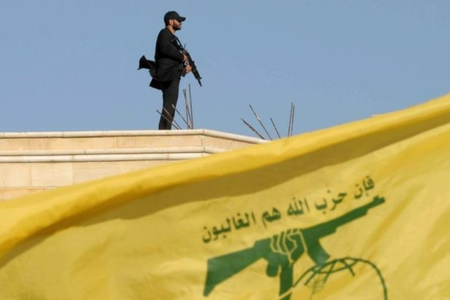 A Hezbollah member carries his weapon on top of a building on May 25, 2016. (photo credit: HASSAN ABDALLAH / REUTERS)