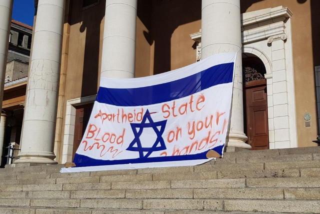 A bloodied Israeli flag hangs on the main building at the University of Cape Town on Monday at the start of Israel-Apartheid Week. (photo credit: SAUJS/FACEBOOK)
