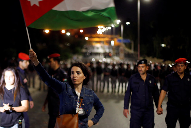 A protester holds up a Jordanian national flag during a protest in Amman, Jordan June 4, 2018 (photo credit: MOHAMMAD HAMED / REUTERS)