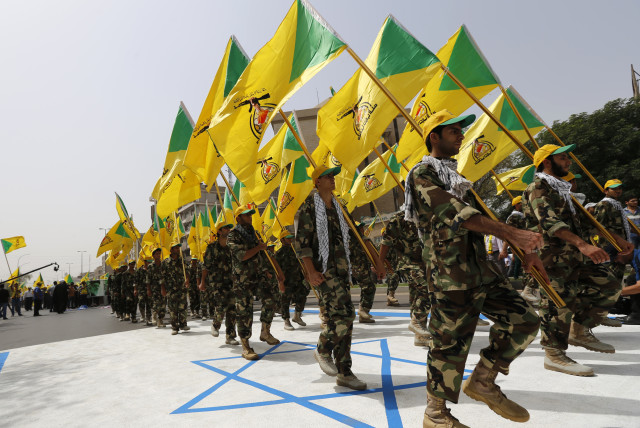 Iraqi Shi'ite Muslim men from the Iranian-backed group Kataib Hezbollah wave the party's flags as they walk along a street painted in the colours of the Israeli flag during a parade marking the annual Quds Day, or Jerusalem Day, on the last Friday of the Muslim holy month of Ramadan, in Baghdad (photo credit: THAIER AL-SUDANI/REUTERS)