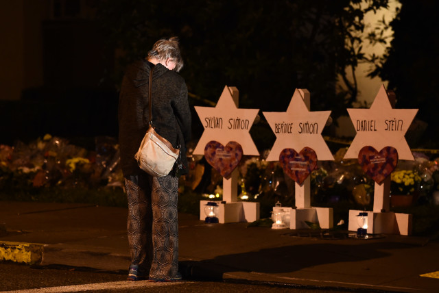 A woman bows her head in front of a memorial on October 28, 2018, at the Tree of Life synagogue after a shooting there left 11 people dead in the Squirrel Hill neighborhood of Pittsburgh on October 27 (photo credit: BRENDAN SMIALOWSKI / AFP)