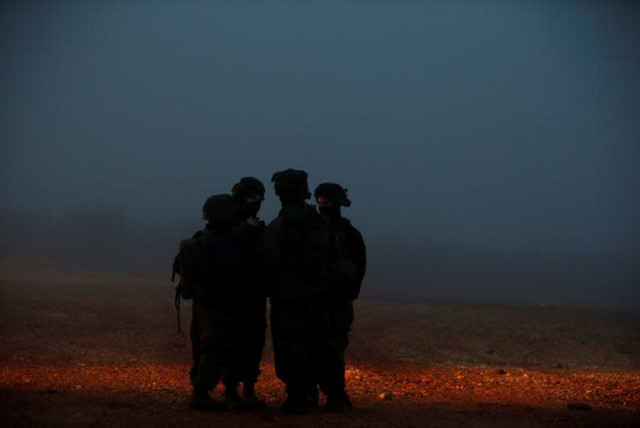 Israeli soldiers stand near the area where Israeli military personnel continue their work on exposing and thwarting cross-border tunnels dug from Lebanon into Israel, as seen on the Israeli side of the border, near the town of Metula December 19, 2018 (photo credit: RONEN ZVULUN / REUTERS)