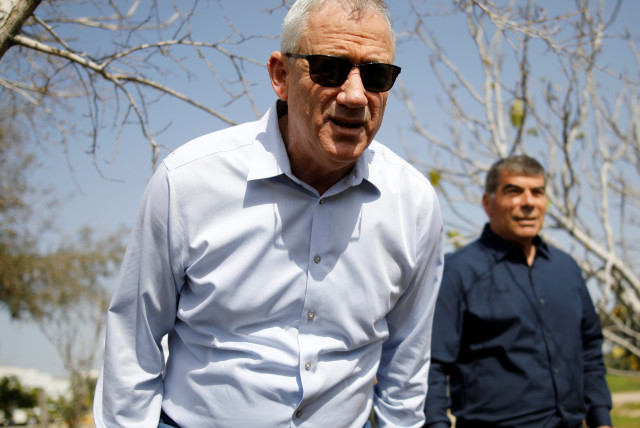 Benny Gantz, head of Blue and White party, leans forward as his party candidate Gabi Ashkenazi stands nearby during a visit to Kibbutz Kfar Aza, outside the northern Gaza Strip, in southern Israel March 13, 2019 (photo credit: AMIR COHEN/REUTERS)