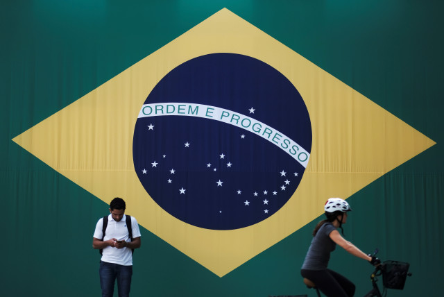 A man checks his mobile phone as a woman riding a bike passes next to a big Brazilian flag in Sao Paulo, Brazil June 28, 2018. (photo credit: REUTERS/NACHO DOCE)