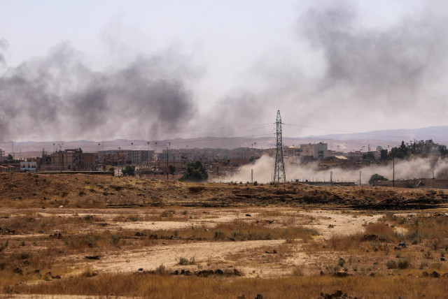Smoke rises after what Kurdish People's Protection Units (YPG) fighters said was shelling by them on locations controlled by Islamic State fighters in Ghwayran neighborhood in Hasaka city, Syria July 22, 2015. A Syrian Kurdish militia said on Monday it was in near full control of the northeastern ci (photo credit: REUTERS/RODI SAID)