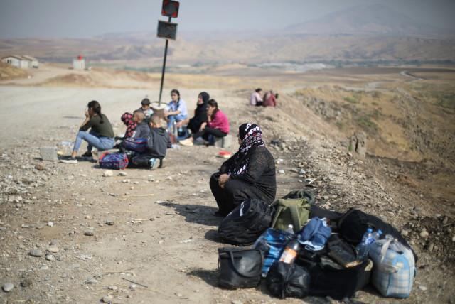 Displaced Kurds stuck at a border after a Turkish offensive in northeastern Syria, wait to try cross to the Iraqi side, at the Semalka crossing, next Derik city, Syria, October 21, 2019 (photo credit: REUTERS/MUHAMMAD HAMED)