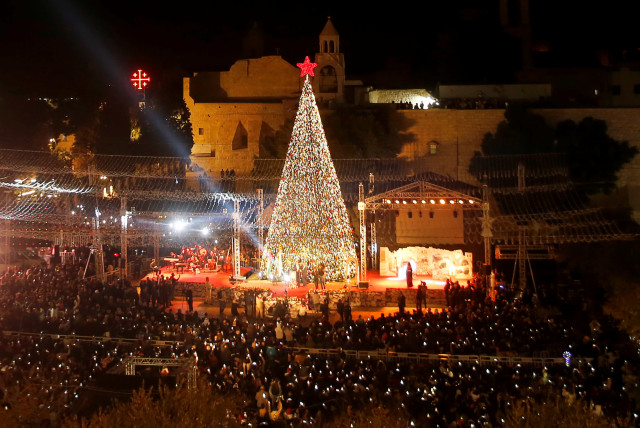 Palestinians light Christmas tree in Manger Square outside the Church of the Nativity in Bethlehem, November 30, 2019 (photo credit: REUTERS/MUSSA QAWASMA)